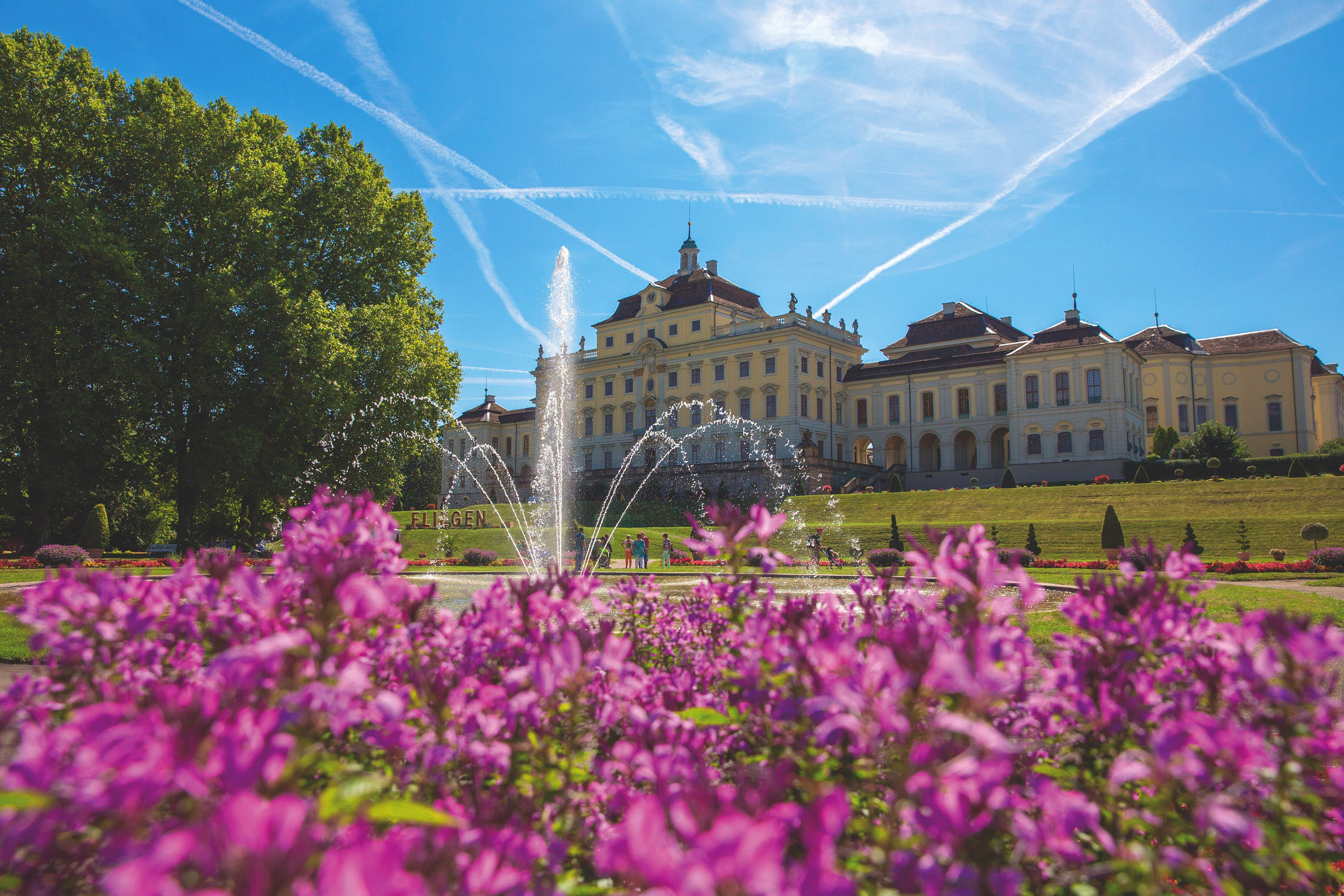 Flowers blooming outside Residenzschloss, Ludwigsburg, Germany. A fountain is visible, as are people walking in the distance.