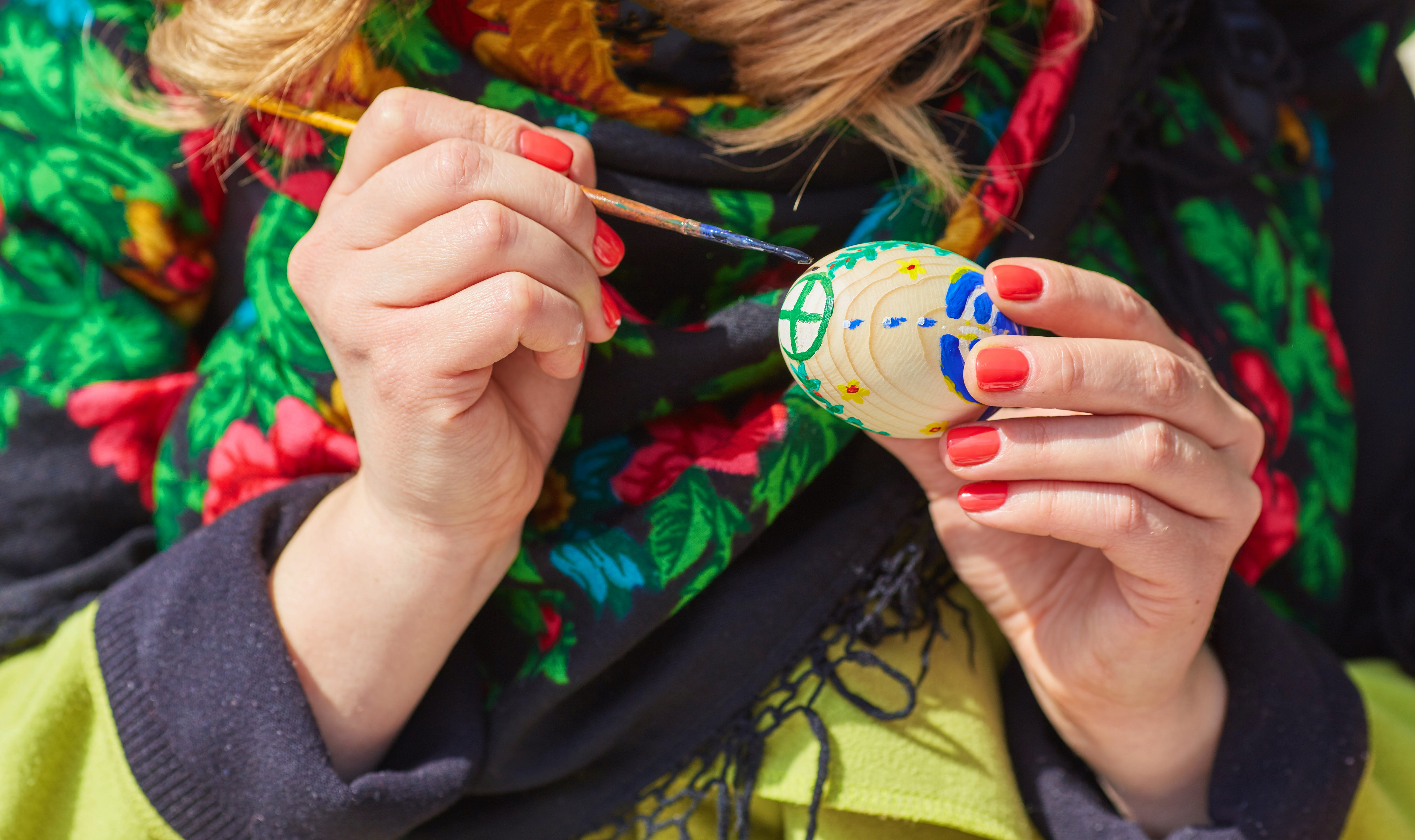 A woman using a fine paintbrush to paint the shell of a hard-boiled egg with an intricate, traditional folk design.