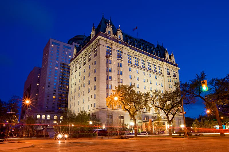An exterior view of the Fort Garry Hotel at night. There are a pair of trees and glowing street lamps in front of the hotel; haunted places world