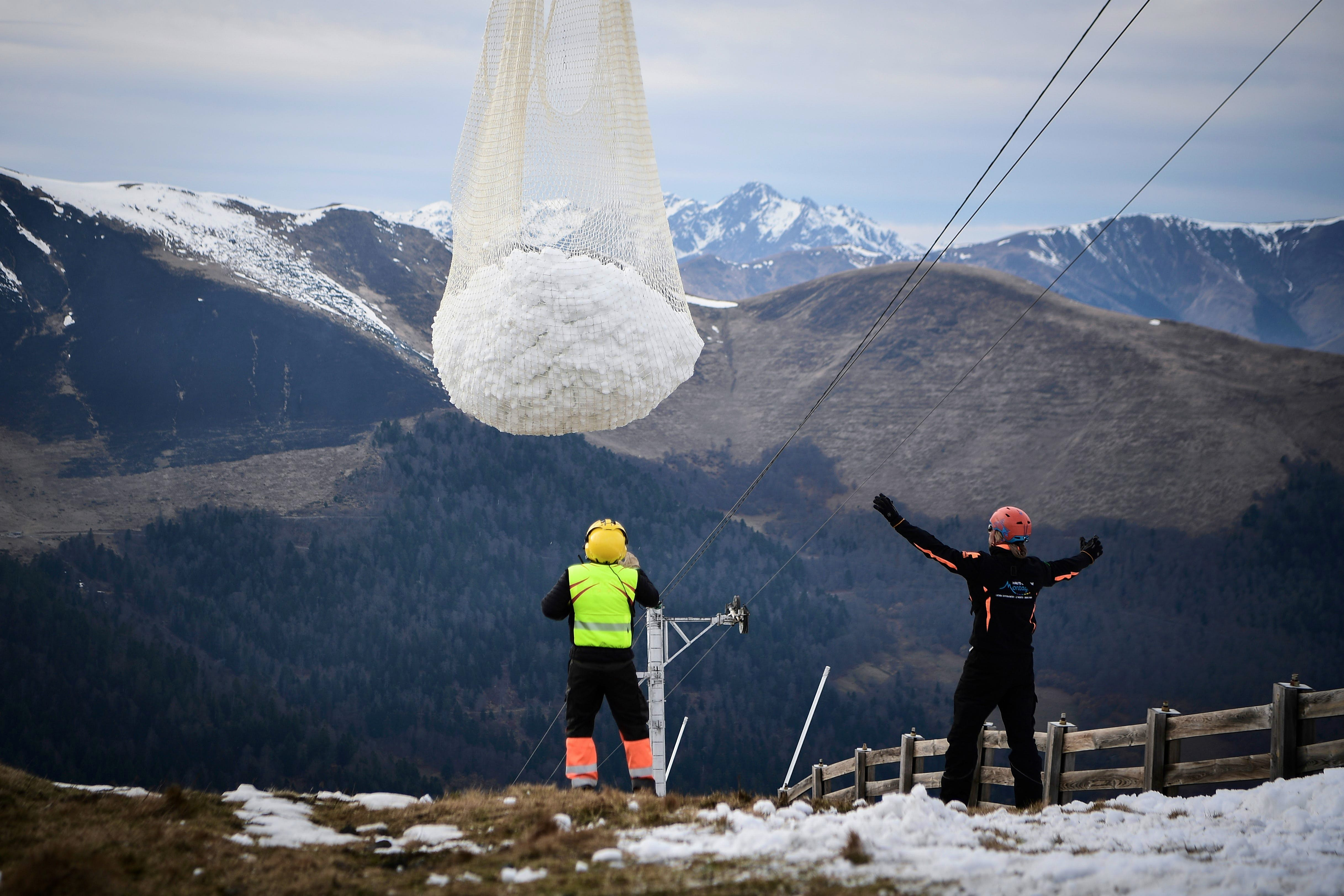 People look at an helicopter carrying snow in order to place it on a ski slope in the Superbagneres station
