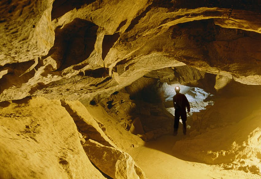 The silhouette of a man wearing a head torch can be seen walking through a narrow passageway in a cave system. The cave walls are a sandy-yellow color.