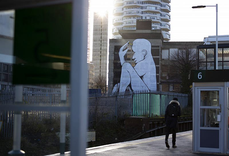 A teenager walking along a train station platform, with tower blocks visible beyond; on one of them is emblazoned a huge mural of a naked seated white figure.