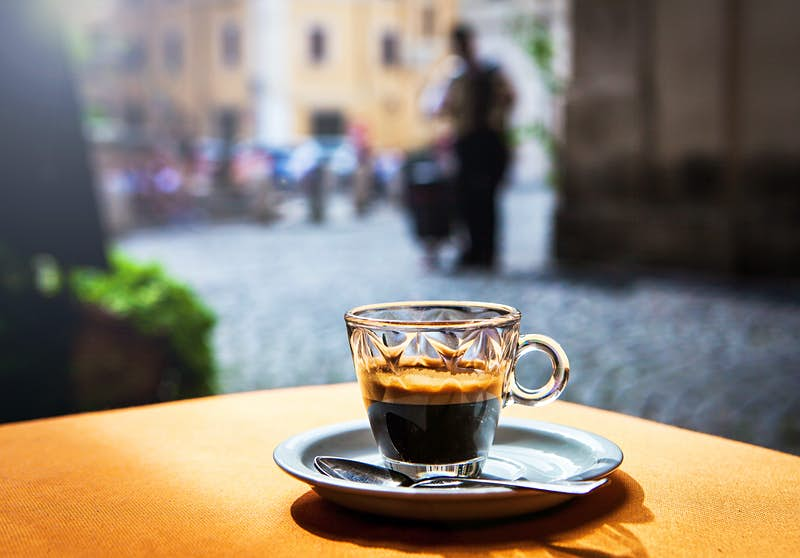 An espresso in a decorative glass cup sitting on a saucer on a table outside. The street scene in the background is in soft focus.