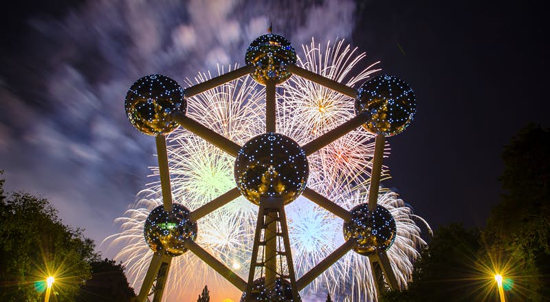A large metal sculpture in the shape of an atom with six big silver balls connected to a larger, central sphere by metal rods is lit by both a series of lights arranged in similar atomic patterns on the surface of each sphere and by a bright fireworks display behind the Atomium against a deep cobalt sky