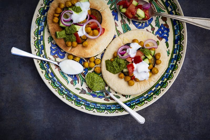 A colourful plate has been artfully arranged with two toasted pita breads, topped with chickpeas, onions, cucumber, tomato and fried eggplant.