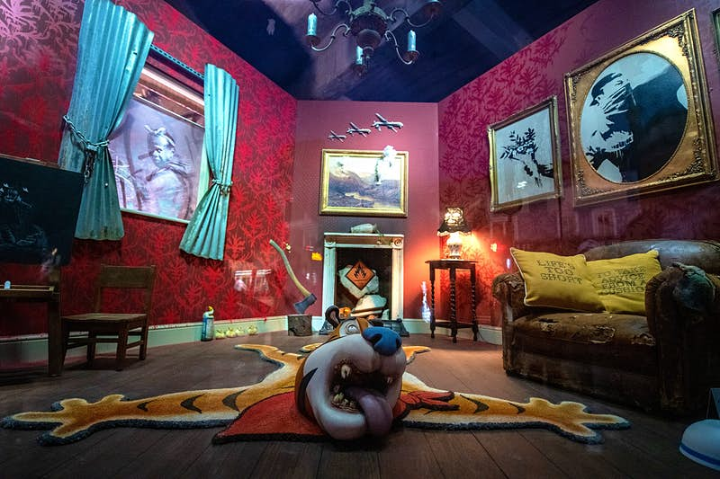 A living room with red walls containing a number of unusual objects, including a rug seemingly made from the body of cereal character Tony the Tiger, and an axe sunk into a tree stump.