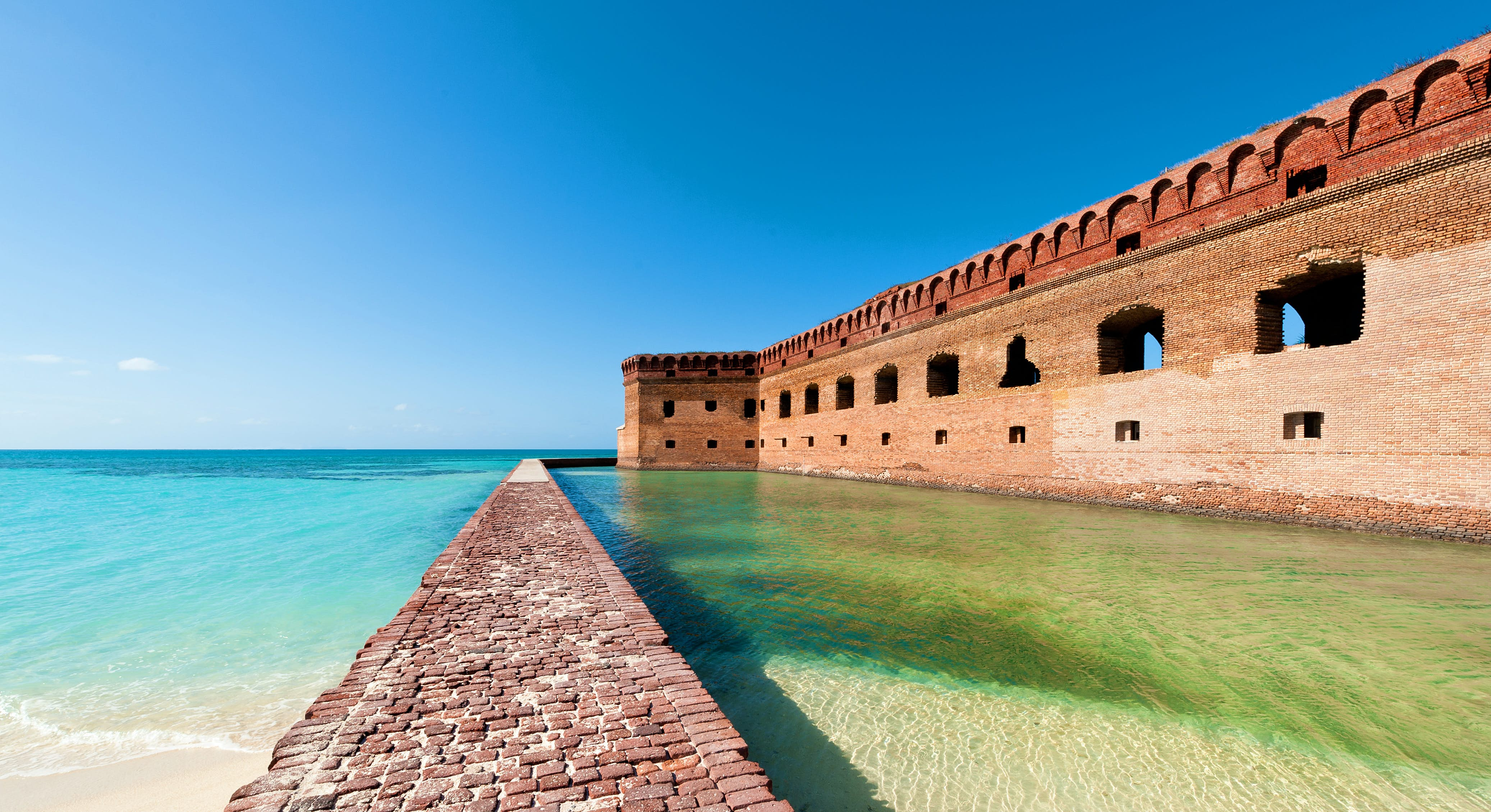 A brick walkway and the imposing Fort Jefferson, contrasting against crystal-clear water in Dry Tortugas National Park near Key West, Florida