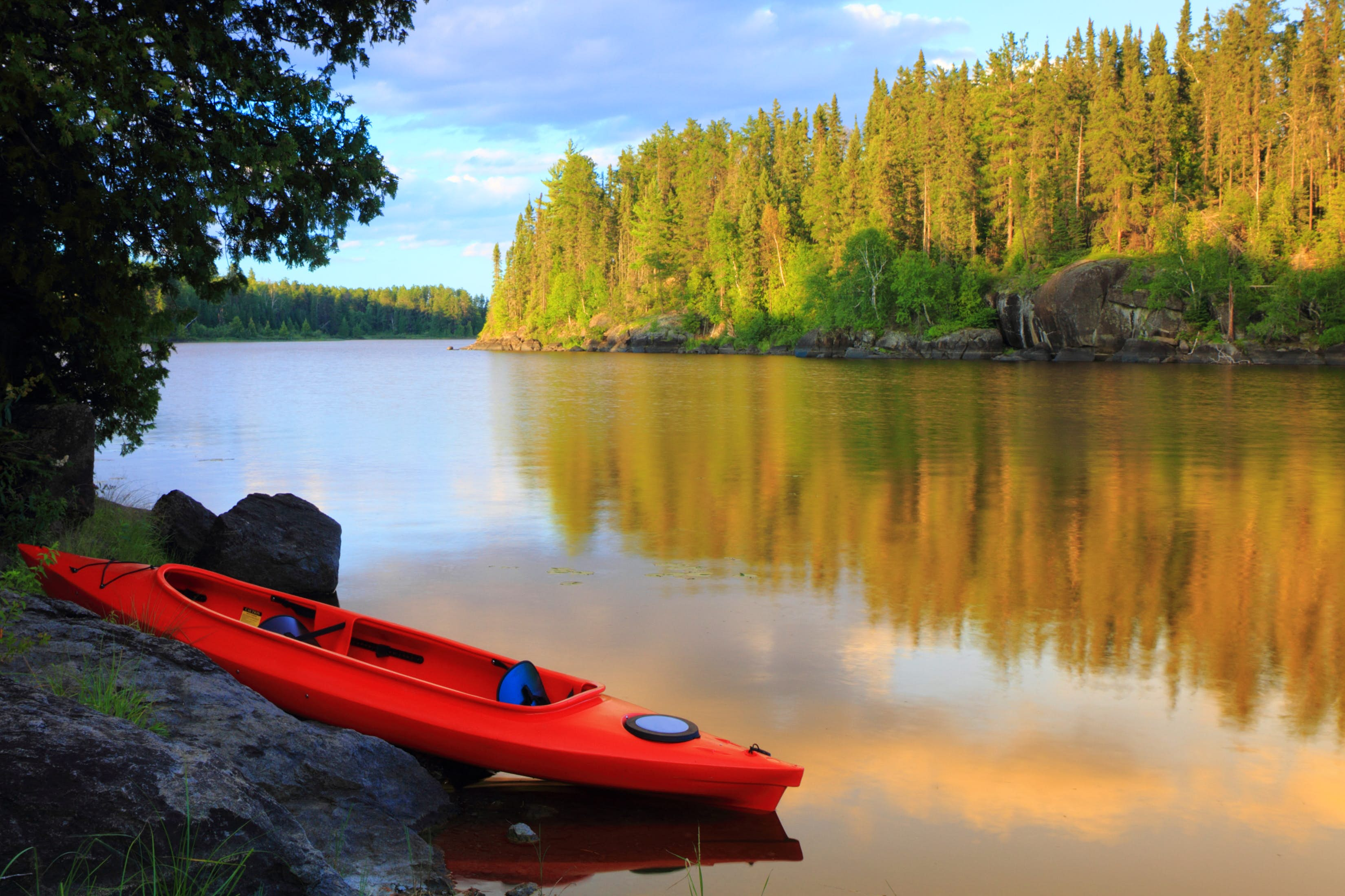 Red canoe sitting on the rocks by a still body of water in Voyageurs National Park, Minnesota