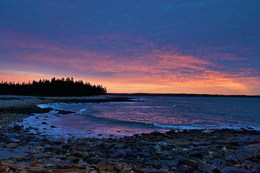 A brilliant sherbert pink and orange sunset reflects of dark blue clouds over Otter Bay in Acadia National Park in Maine. The ocean reflects the sunset in muted tones and a tall stand of trees is jet black in the background. Scuba diving in national parks
