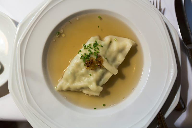 A pale dumpling topped with dark brown spices and bright green herbs sits in a pool of golden broth in a large white serving dish on a white table cloth.