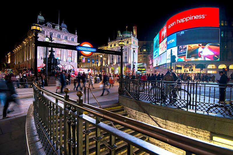Long exposure of pedestrians and traffic outside Piccadilly Circus tube station in London,