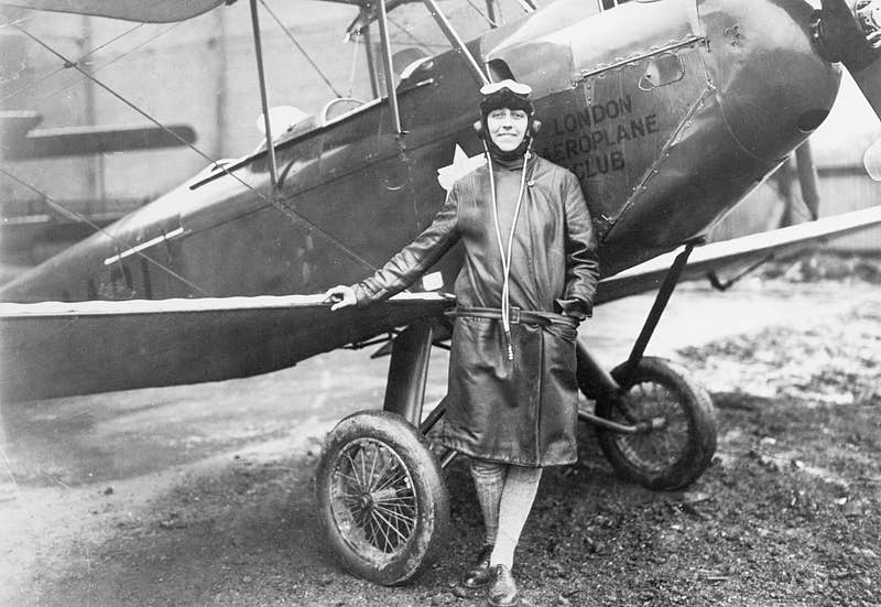 Black-and-white image of a woman wearing a three-quarter length coat with flight goggles on her head standing near a biplane