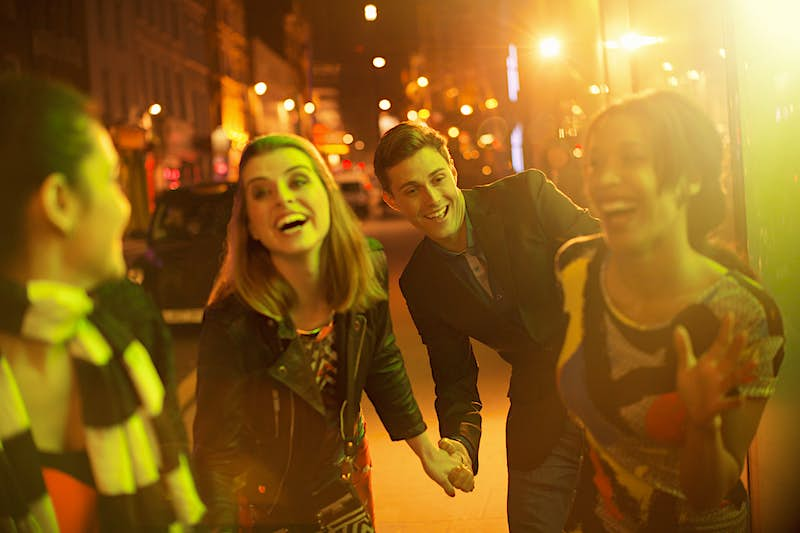Friends walking down city street together at night
