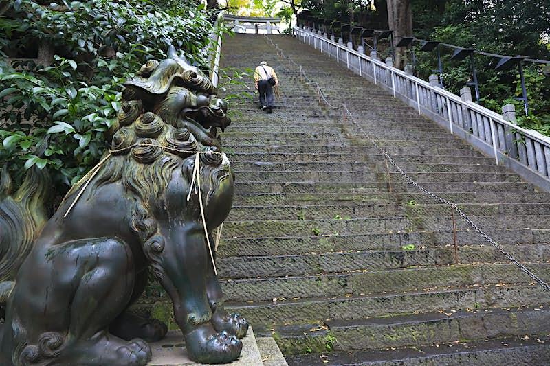 Một bộ dài các bước bê tông trải dài lên trên, với một cổng vào một ngôi đền chỉ có thể nhìn thấy ở trên cùng. Một người đàn ông đang leo lên các bậc thang. Một bức tượng lớn như sư tử ở dưới cùng của các bước