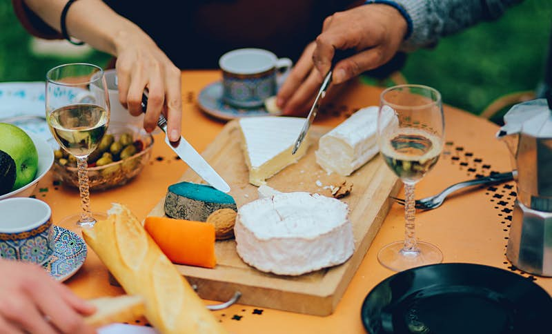 A tabletop showing a selection of bread, cheeses, olives and wine glasses. Diners, sitting around it, are poised with butter knives, ready to dig in.