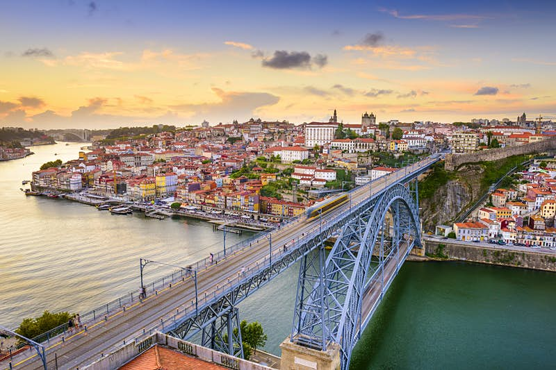 The Dom Luis Bridge stretches out over the rippling waters of the Douro river at sunset.
