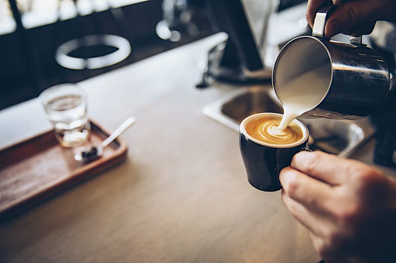 A close-up shot of a barista pouring milk into a small coffee cup over a wooden counter top.