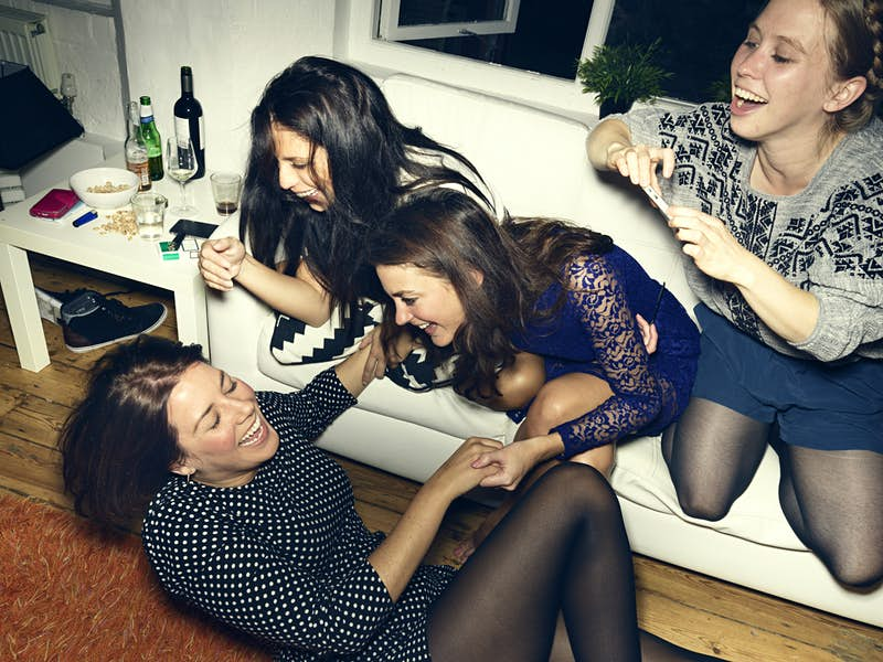 Group of young people having a party, telling jokes, having a good time, celebrating, in a private home
