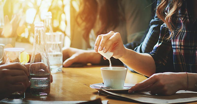 A woman pours a sachet of sugar into a cup of coffee.