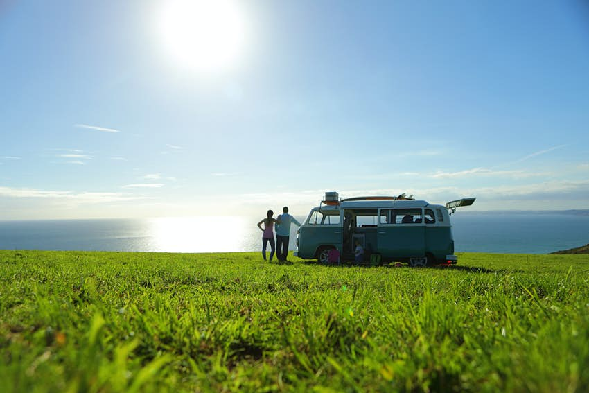 Two people stand next to a classic VW camper van parked in the middle of a grassy field. The sea is visible in the distance.