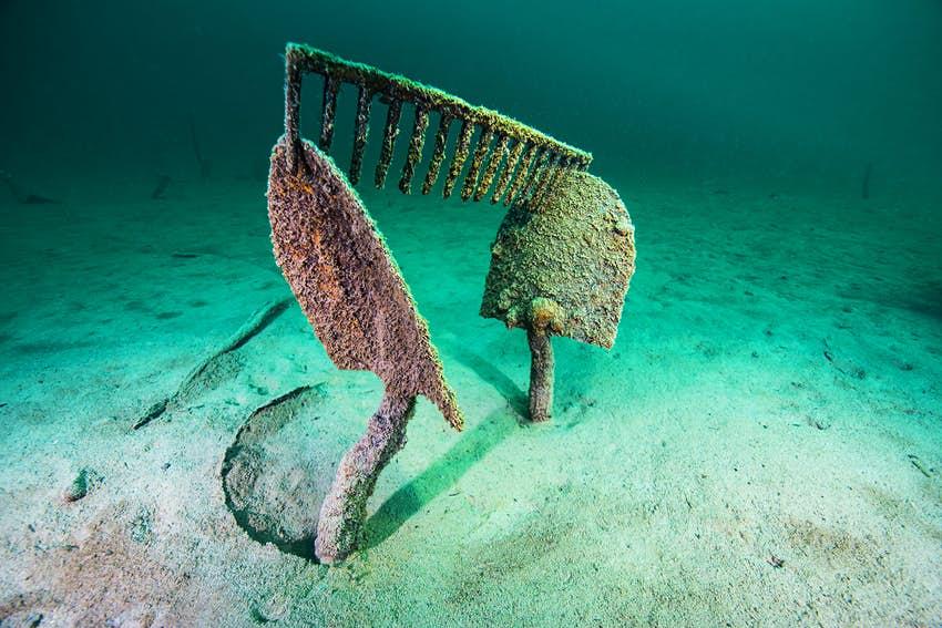 Two shovels, rusted and covered in marine sediment, stand straight up from the bed of Lake McDonald, with an equally rusted rake head perched on top. All around are the deep teal and bright aqua waters found throughout Glacier National Park