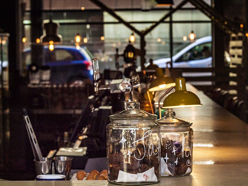 A warmly lit bar in a coffee shop, with utensils in pots and two large glass jars containing chocolate brownies.