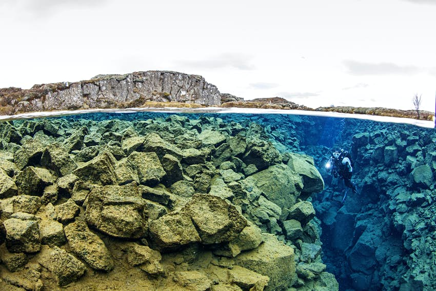 The top third of the shot shows the grey, rocky shore around the Silfra Fissure in Thingvellir National Park, while the bottom two thirds show what's under water, with a gradient of the tan, grey, turquoise, and deep lbue waters that are perfectly clear, and show a diver with a white light between two tectonic plates that form a narrow, rocky canyon