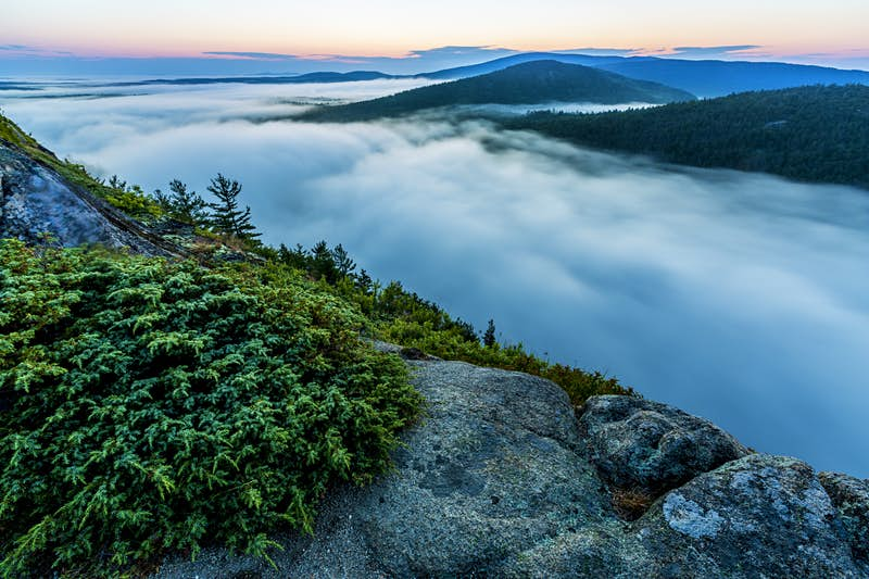 Fog rolls in along a lake in Acadia National Park, but we're on top of a mountain above the cloud; Maine backwoods adventures