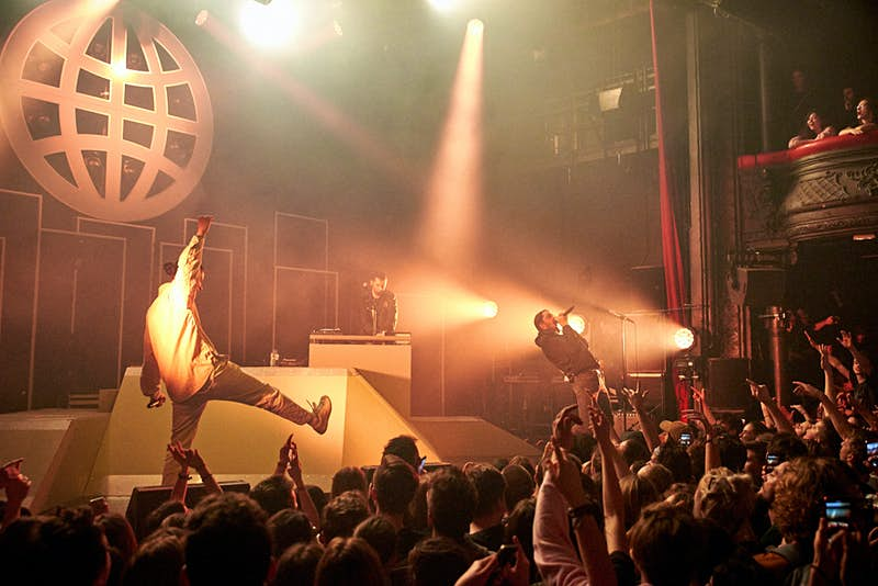 A rap group performs on the stage of La Cigale in Paris. An animated crowd, in shadow beneath the stage, watch on.