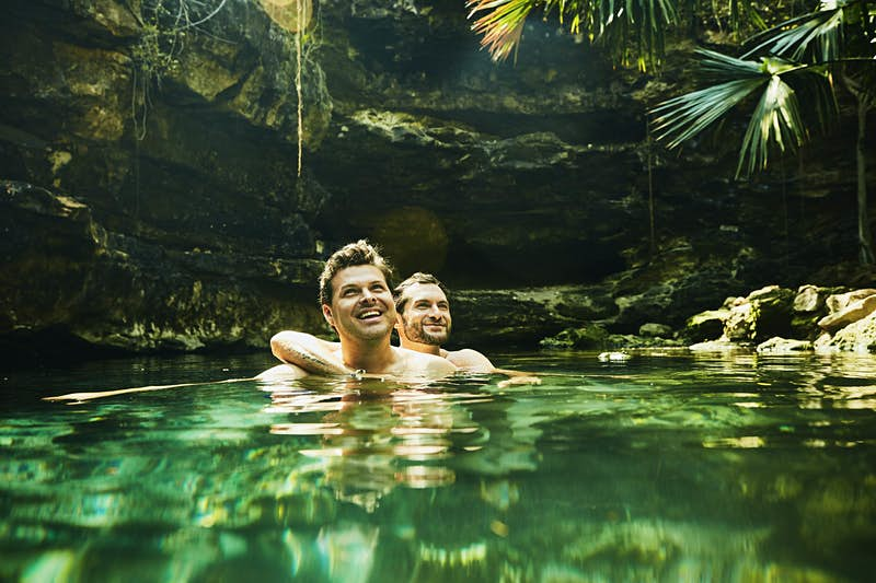 A smiling couple are swimming in the blue-green waters of a cenote. Sun shines down into the pool and highlights the two men as one is embracing the other.