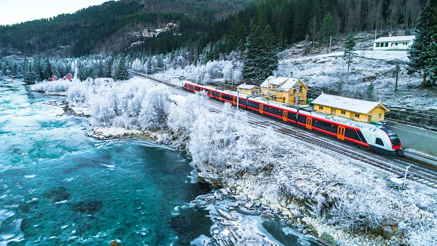 Train traveling in Norway past a blue lake and snow-covered trees