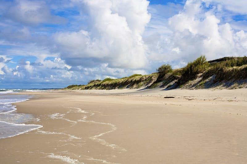 An empty beach stretches into the distance. Sand dunes covered in grass are on the right; the Baltic Sea is on the left