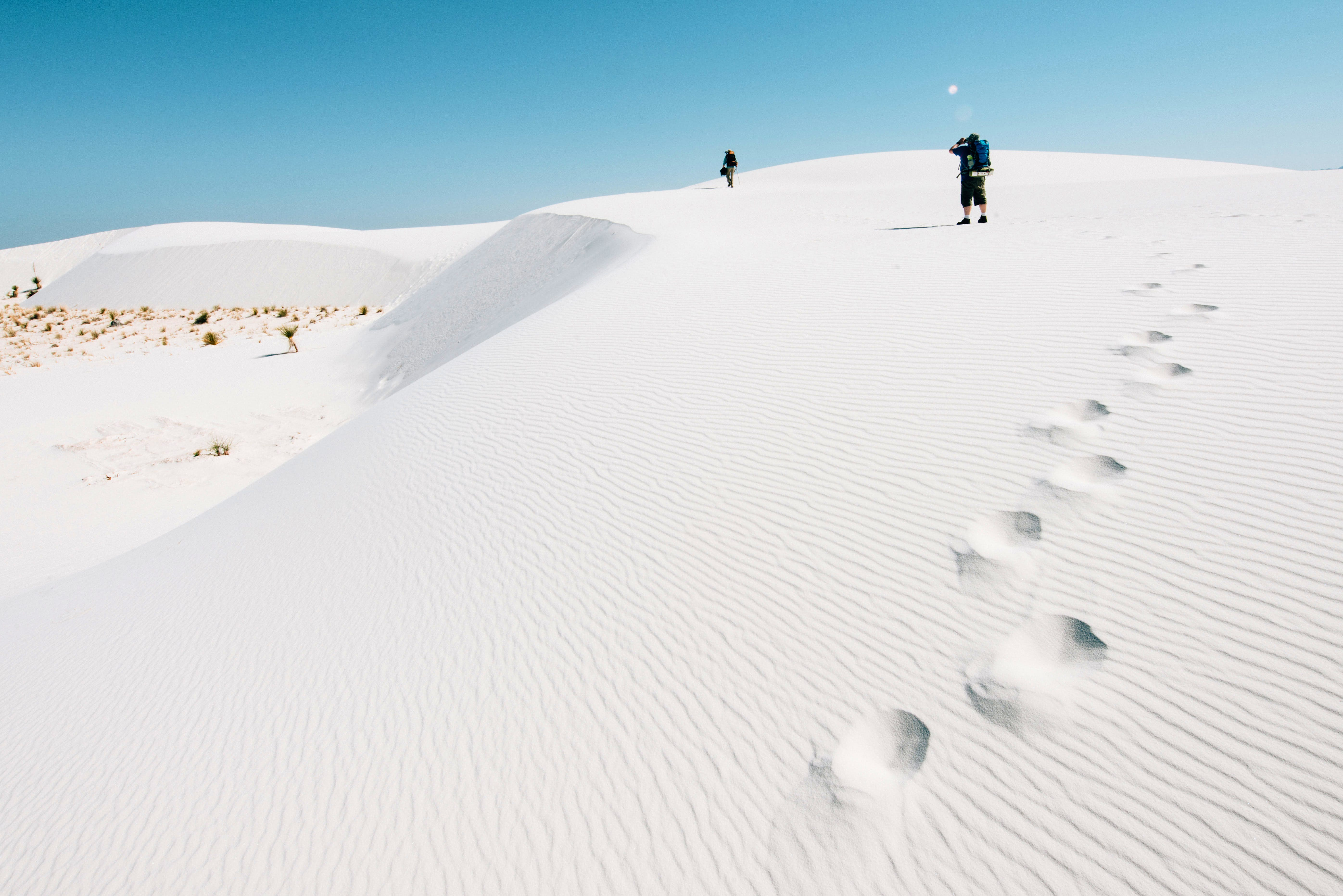 Backpackers hiking on bright white sand dunes at White Sands National Monument in New Mexico