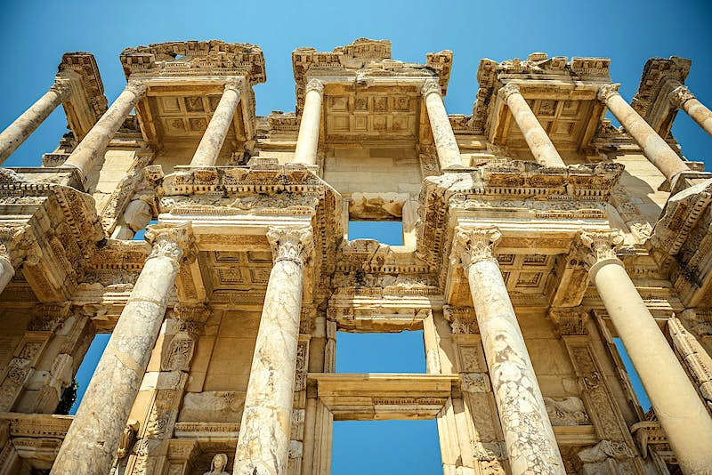 Looking up at the ornate, pillared façade of the Library of Celsus at Ephesus.