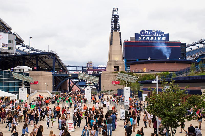 A group of people walk and stand around a concourse at Gillette Stadium in Foxborough; nfl cities travel