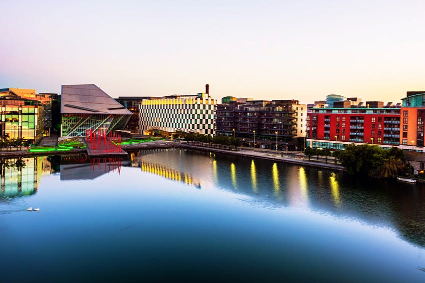 Modern buildings surround a very still dock in Dublin as the sun rises and lights up a pale sky