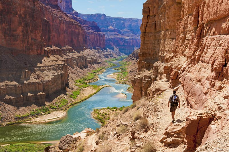 A man walks down the rocky slope of the Grand Canyon toward the Colorado River
