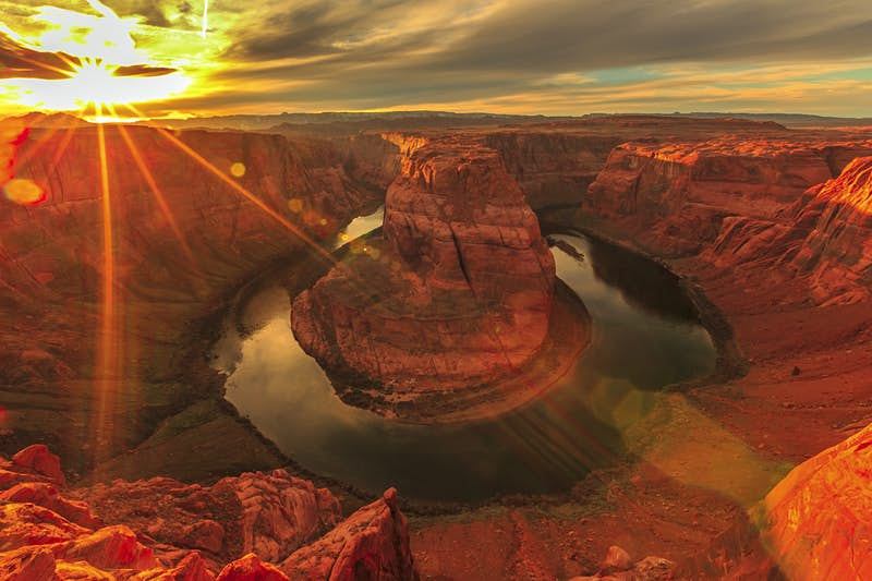 A stunning sunset highlights the rock formations around Horseshoe Bend in the Grand Canyon