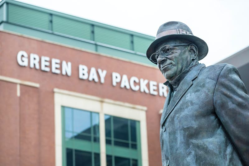 A statue of Green Bay Packers coaching great, Vince Lombardi, stands in front of Lambeau Field; nfl cities travel