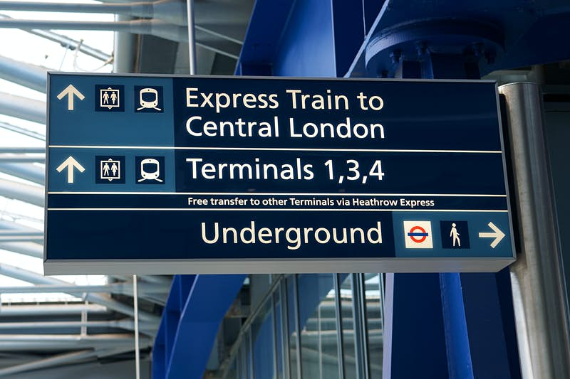 Blue and white sign with a series of icons and words 'express train to central London' 'Terminals 1,3,4' and 'Underground'