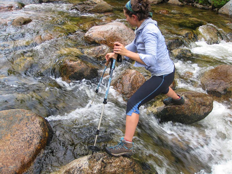A woman uses poles to help her hike along a creek in the Maine backwoods