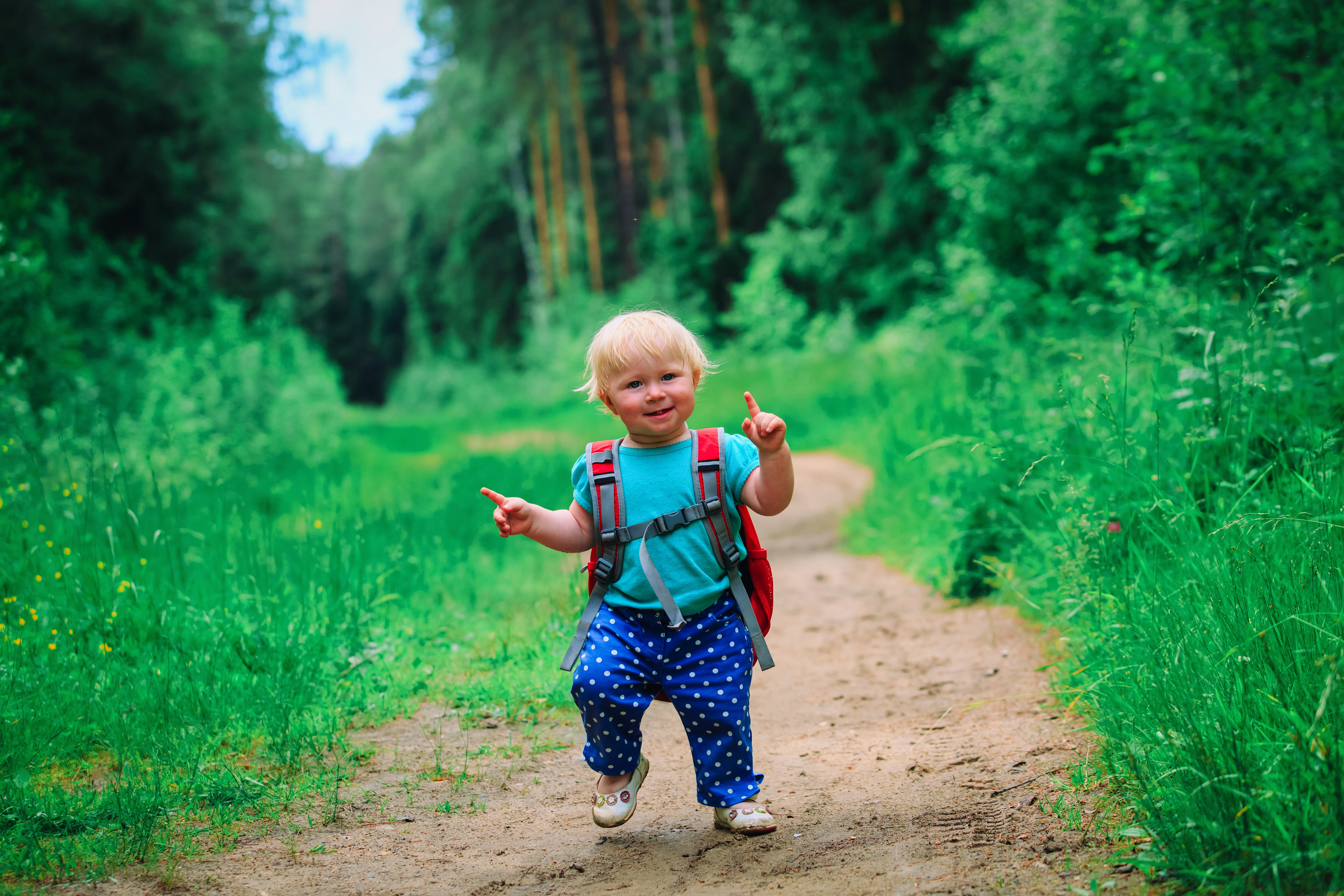 A toddler bebops down a trail with an oversized backpack on; kids outdoor activities