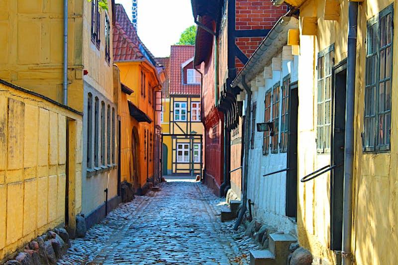Uma rua estreita de paralelepípedos em Møntergården, Odense, com edifícios pintados de cores vivas.