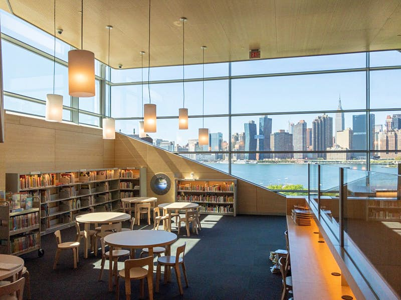 The interior of Hunters Point Community Library in New York complete with books and seating