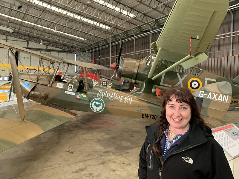 A female pilot stands near her aircraft which is in a hangar. The plane is predominantly brown in colour with several colourful stickers, including one that says Ivy (the name of the plane) and RVH (the initials of the pilot's father)