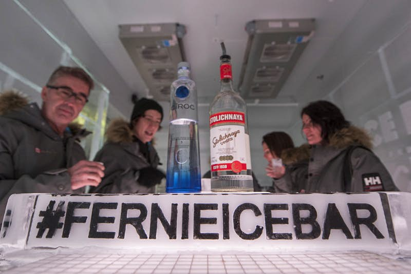 Five people are seated around a table in an ice bar, chatting. One of the people is obscured by two bottles of alcohol in the foreground. In front of those bottles is a sign made of ice with the bar's official hashtag.
