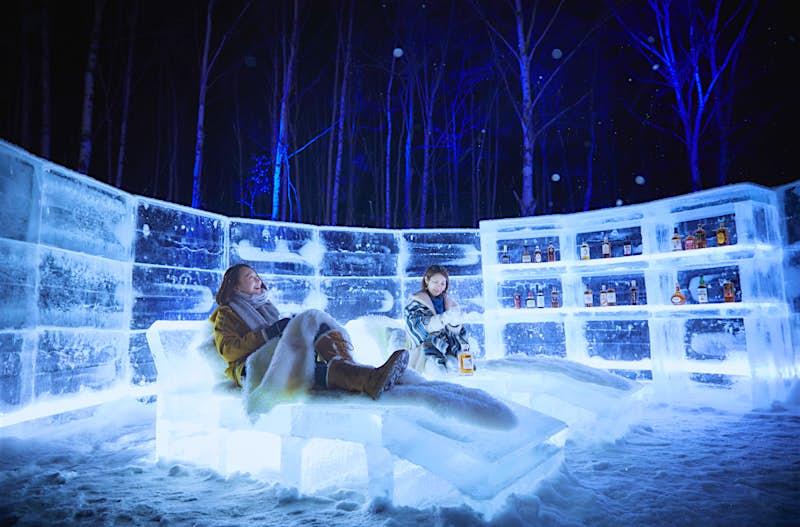 As pessoas sentam-se em blocos de gelo no Ice Hotel Tomamu no Japan.jpg