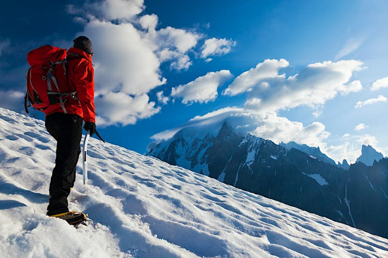 A man stands on a snowy mountain overlooking another snow-capped mountain