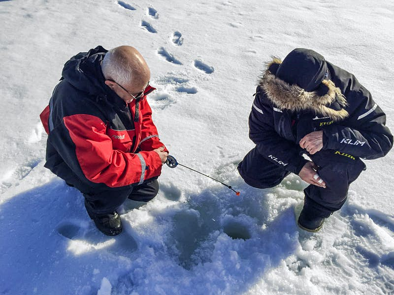 A pair of men sit in front of a hole drilled into the ice for ice fishing