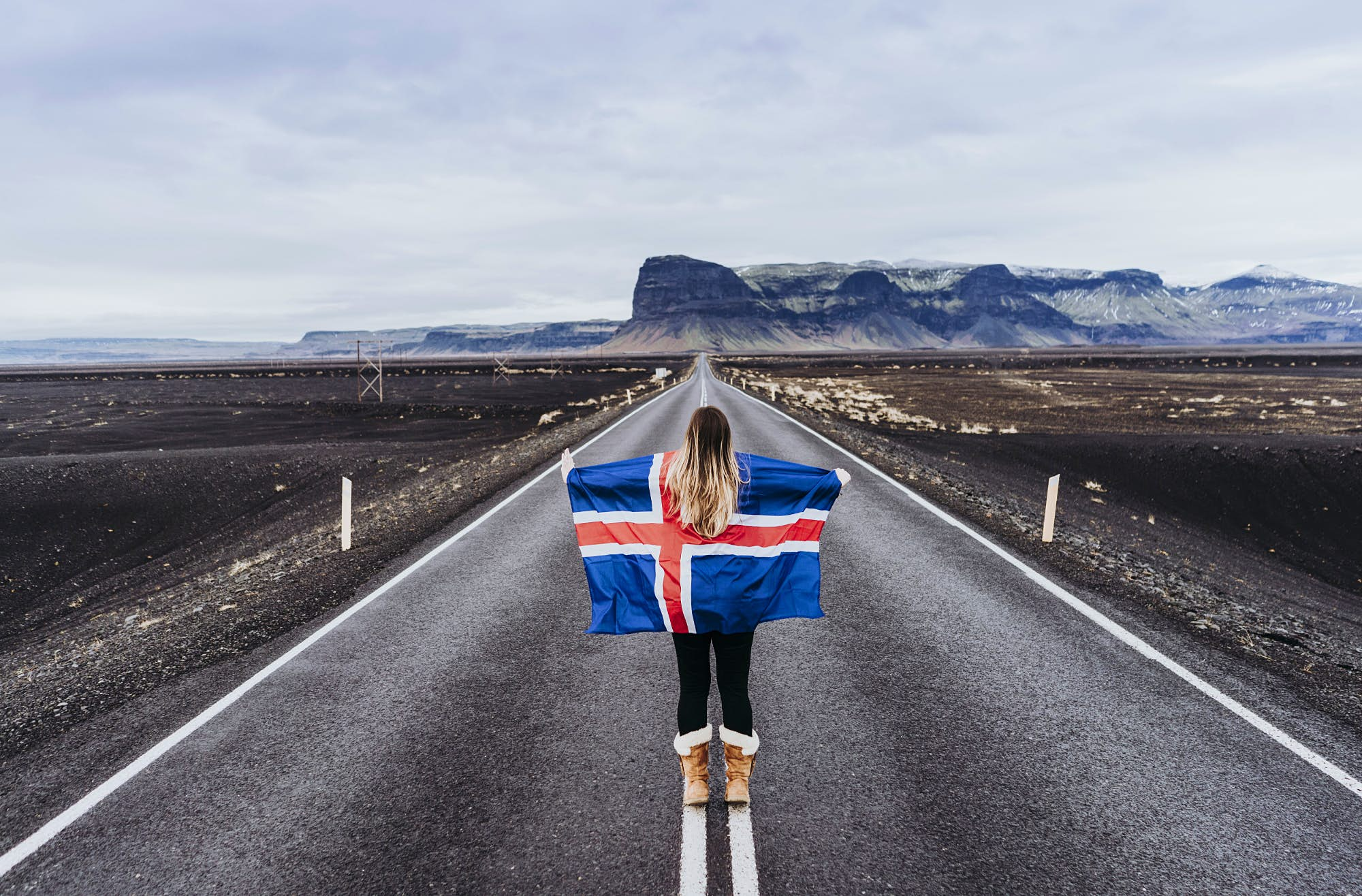a woman holds an Icelandic flag on a road